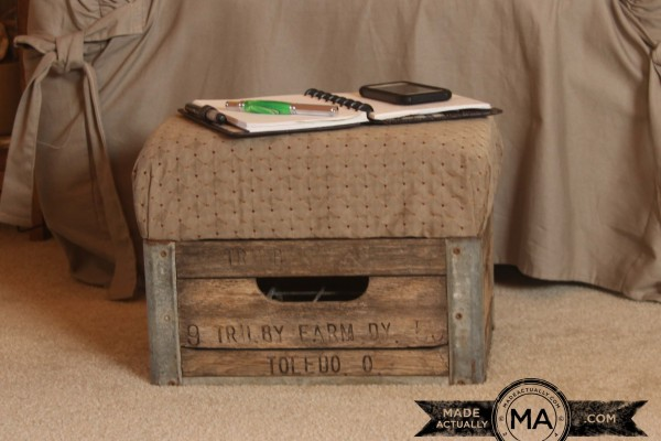Antique milk crate transormed into a footstool or ottoman